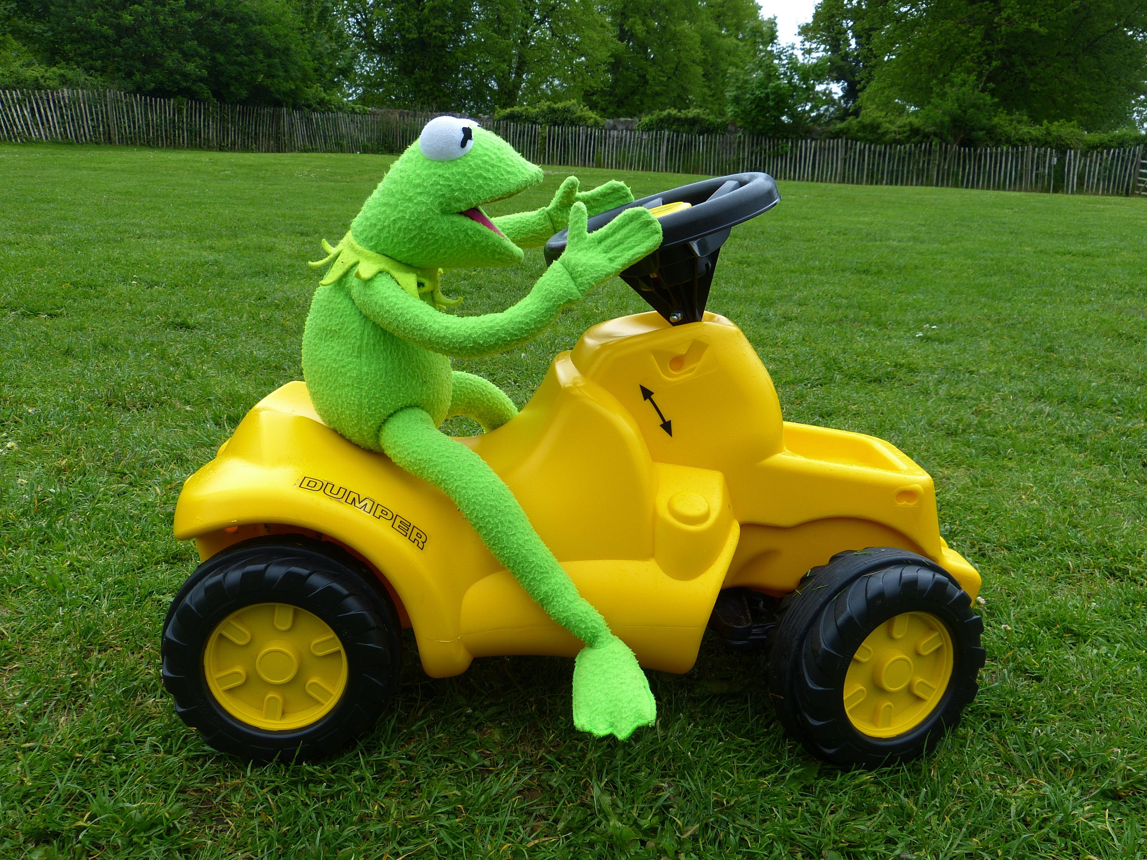 En kermitgroda på en gul leksaksbil.